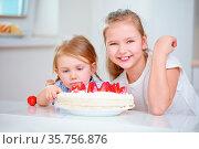 Kinder naschen heimlich vom Erdbeerkuchen in der Küche. Стоковое фото, фотограф Zoonar.com/Robert Kneschke / age Fotostock / Фотобанк Лори