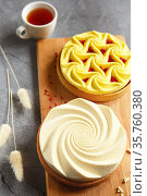 Delicious mini tarts yellow and white with nuts and custard on wooden cutting board. Assortment of delicious and colorful dessert, lemon curd tart, cream chocolate tart made by chef. Стоковое фото, фотограф Nataliia Zhekova / Фотобанк Лори