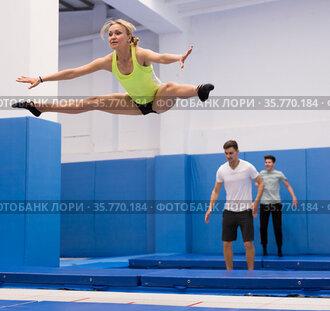 Woman practicing side split on trampoline