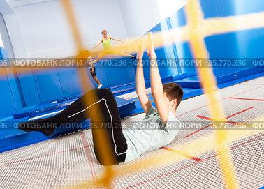 Teenager practicing alternate landings on trampoline