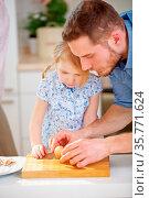 Vater zeigt Tochter in der Küche wie ein gekochtes Ei geschält wird. Стоковое фото, фотограф Zoonar.com/Robert Kneschke / age Fotostock / Фотобанк Лори