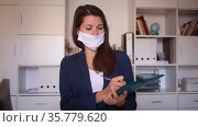 Female business assistant wearing medical face mask standing in office with clipboard, noting tasks. Стоковое видео, видеограф Яков Филимонов / Фотобанк Лори