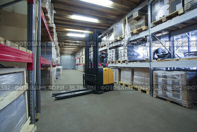 Warehouse interior with racks, boxes and forklift
