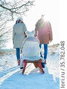 Glückliches Kind beim Schlitten fahren mit Eltern im Winter im Schnee. Стоковое фото, фотограф Zoonar.com/Robert Kneschke / age Fotostock / Фотобанк Лори