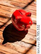 Ein rotes Sparschwein steht auf einem Holzboden und wirft einen starken... Стоковое фото, фотограф Zoonar.com/ironjohn / easy Fotostock / Фотобанк Лори