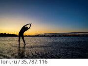 Practicing yoga palm tree pose - sunrise silhouette of a man on a... Стоковое фото, фотограф Zoonar.com/Marek Uliasz / easy Fotostock / Фотобанк Лори