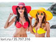 Two female friends in bikini sunhat and sunglasses on tropical beach... Стоковое фото, фотограф Zoonar.com/Ivan Mikhaylov / easy Fotostock / Фотобанк Лори