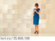 Attractive woman in blue dress standing against modern wall while... Стоковое фото, фотограф Zoonar.com/Danil Roudenko / age Fotostock / Фотобанк Лори