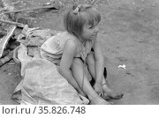 Child of white migrant worker sitting on cotton pickers' sacks near Harlingen, Texas by Russell Lee, 1903-1986, dated 19390101. Редакционное фото, агентство World History Archive / Фотобанк Лори