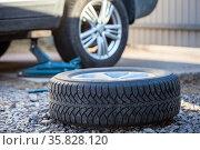Seasonal winter tyre change. Snow tire lying on ground, is ready to install, spring. Стоковое фото, фотограф Кекяляйнен Андрей / Фотобанк Лори