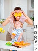 Familie mit Mutter und Tochter hat Spaß beim Saft pressen in der Küche. Стоковое фото, фотограф Zoonar.com/Robert Kneschke / age Fotostock / Фотобанк Лори