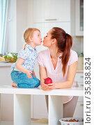 Glückliche Mutter und kleine Tochter küssen sich in der Küche. Стоковое фото, фотограф Zoonar.com/Robert Kneschke / age Fotostock / Фотобанк Лори