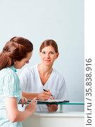 Ältere Ärztin füllt ein Formular mit einer Patientin zusammen aus. Стоковое фото, фотограф Zoonar.com/Robert Kneschke / age Fotostock / Фотобанк Лори