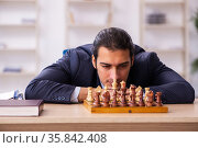 Young male employee playing chess at workplace. Стоковое фото, фотограф Elnur / Фотобанк Лори
