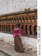 Woman with baby on back spinning prayer wheels at Changangkha Lhakhang Monestary, 'The Fertility Temple'. Bhutan. September 2013. Стоковое фото, фотограф Jeff Foott / Nature Picture Library / Фотобанк Лори