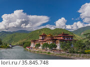 Bridge to Punakha Dzong, built on the confluence of the Mo Chhu (female) and Pho Chhu (male) rivers, Bhutan. September 2013. Стоковое фото, фотограф Jeff Foott / Nature Picture Library / Фотобанк Лори