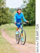 Aktive Seniorin beim Fahrrad fahren in der Natur. Стоковое фото, фотограф Zoonar.com/Robert Kneschke / age Fotostock / Фотобанк Лори