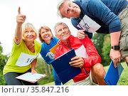 Senioren mit Klemmbrett bei einem Geocaching Spiel oder einer Schnitzeljagd. Стоковое фото, фотограф Zoonar.com/Robert Kneschke / age Fotostock / Фотобанк Лори