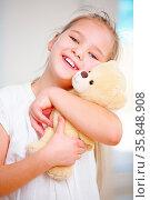 Glückliches Mädchen kuschelt sich an ihr Kuscheltier zu Hause. Стоковое фото, фотограф Zoonar.com/Robert Kneschke / age Fotostock / Фотобанк Лори