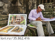An artist painting in Angkor Thom Temple. Siem Reap. Cambodia (2020 год). Редакционное фото, фотограф Marco Brivio / age Fotostock / Фотобанк Лори