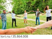 Junges glückliches Team bildet einen Kreis im Park in einem Teambuilding... Стоковое фото, фотограф Zoonar.com/Robert Kneschke / age Fotostock / Фотобанк Лори