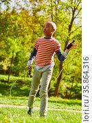 Afrikanischer Junge spielt mit dem Springseil im Park in den Sommer... Стоковое фото, фотограф Zoonar.com/Robert Kneschke / age Fotostock / Фотобанк Лори
