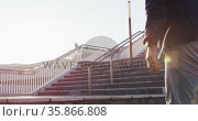 Low section of asian man with backpack climbing up the stairs at corporate park. Стоковое видео, агентство Wavebreak Media / Фотобанк Лори