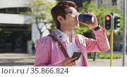 Asian man drinking coffee and using smartphone while crossing the street. Стоковое видео, агентство Wavebreak Media / Фотобанк Лори