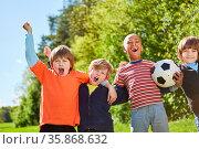 Kinder im multikulturellen Fußball Team freuen sich über einen Sieg... Стоковое фото, фотограф Zoonar.com/Robert Kneschke / age Fotostock / Фотобанк Лори