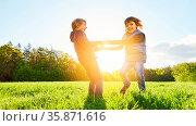 Zwei Kinder halten Hände und tanzen auf einer Wiese im Sommer. Стоковое фото, фотограф Zoonar.com/Robert Kneschke / age Fotostock / Фотобанк Лори