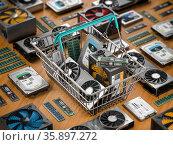 Computer hardware in shopping basket. Buying pc computer parts online concept. Стоковое фото, фотограф Maksym Yemelyanov / Фотобанк Лори