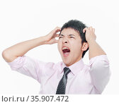 Young man with hands on head screaming. Стоковое фото, агентство Ingram Publishing / Фотобанк Лори