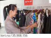 Woman going through clearance clothes at fashion store. Стоковое фото, агентство Ingram Publishing / Фотобанк Лори