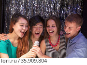 Four friends singing together at karaoke. Стоковое фото, агентство Ingram Publishing / Фотобанк Лори
