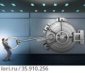 Businessman with key near bank vault door. Стоковое фото, фотограф Elnur / Фотобанк Лори