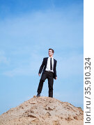 Young solitary businessman standing on a hill in the desert. Стоковое фото, агентство Ingram Publishing / Фотобанк Лори
