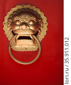 Close-up of ornate gold door knocker on red door. Стоковое фото, агентство Ingram Publishing / Фотобанк Лори