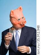 Man in a pig mask eating chocolate. Стоковое фото, фотограф Shannon Fagan / Ingram Publishing / Фотобанк Лори