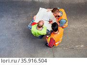 Gruppe Arbeiter mit Bauplan bei der Planung von oben auf einer Baustelle. Стоковое фото, фотограф Zoonar.com/Robert Kneschke / age Fotostock / Фотобанк Лори