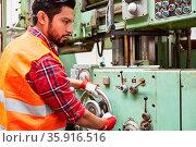 Arbeiter in Fabrik für Metallbau bedient eine Standbohrmaschine über... Стоковое фото, фотограф Zoonar.com/Robert Kneschke / age Fotostock / Фотобанк Лори