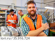 Glücklicher Lagerarbeiter in der Ausbildung im Material Lager der... Стоковое фото, фотограф Zoonar.com/Robert Kneschke / age Fotostock / Фотобанк Лори