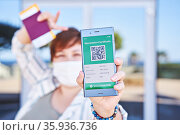 Happy woman holding smartphone displaying on app mobile valid digital green vaccination certificate for Covid-19. Стоковое фото, фотограф Kira_Yan / Фотобанк Лори