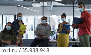 Portrait of diverse group of work colleagues wearing face mask holding laptop, tablet and documents. Стоковое видео, агентство Wavebreak Media / Фотобанк Лори
