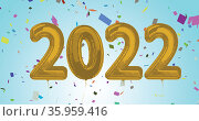 Composition of 2022 gold balloons numbers and confetti on blue background. Стоковое фото, агентство Wavebreak Media / Фотобанк Лори