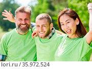 Glückliche junge Leute in grünen Shirts als Umweltschützer Team. Стоковое фото, фотограф Zoonar.com/Robert Kneschke / age Fotostock / Фотобанк Лори