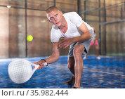 Padel player playing padel in a padel court indoor behind net. Стоковое фото, фотограф Яков Филимонов / Фотобанк Лори