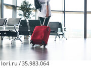 Woman traveler with luggage in airport or train station waiting room; legs and suitcase close-up. Стоковое фото, фотограф Евгений Харитонов / Фотобанк Лори