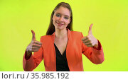 Woman showing double thumbs up, like gesture. Yellow space studio. Стоковое видео, видеограф Gennadiy Poznyakov / Фотобанк Лори