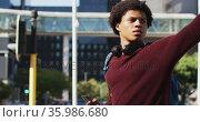 African american man in city using smartphone, wearing headphones and backpack hailing cab in street. Стоковое видео, агентство Wavebreak Media / Фотобанк Лори