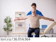 Old male patient visting young male doctor chiropractor. Стоковое фото, фотограф Elnur / Фотобанк Лори